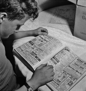 """""""Junk: Scrap salvage campaign.This boy is looking up junk dealers in the telephone directory, wants junk dealer pick up the scrap which he collected stored in his celler Washington, D.C. May 1942."""" by polkbritton is marked with CC PDM 1.0"""